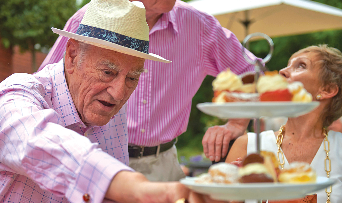Iconic Brand Agency | Market Branding | Elderly man tucking into scones
